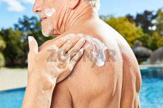 Frau reibt Rücken eines Mannes ein