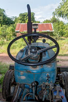 View of the interior of a used tractor with a steering wheel and the control board. Dirty old tractor parked under a shed on the farm