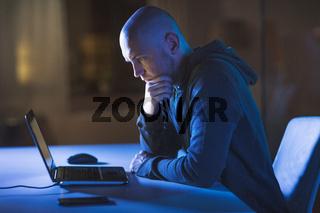 hacker with laptop computer in dark room