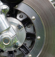 close up of a metal disk brake on the front wheel of an old motorcycle