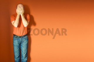 man in front of an orange wall