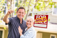 Caucasian Couple in Front of Sold Real Estate Sign and House with Keys