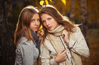 Two young fashion girls in white shirt and scarf in autumn park