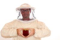 Imker hält Honigglas in der Hand