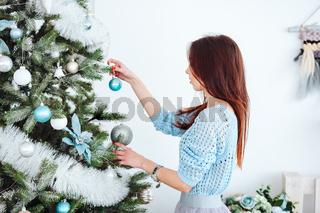 Girl dresses up Christmas tree