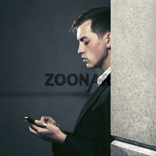 Young handsome business man using smart phone in city street
