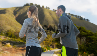 couple with earphones running over big sur