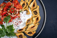 Traditional Armenian manti with mincemeat and paprika tomato salad as top view on a plate with copy space right