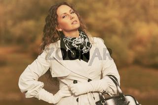 Beautiful fashion woman in white trench coat walking outdoor