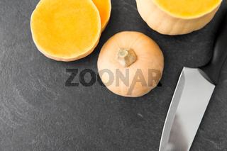 cut pumpkin and kitchen knife on stone background