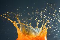 Orange juice crown splash spraying over dark background