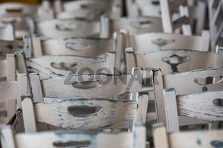 Row of empty white wooden chairs