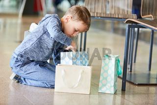 Junge packt neugierig Geschenke aus
