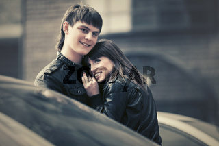 Happy young couple in love walking in city street