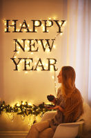 Woman sitting by the Happy New Year Holiday letters. Bright words on the wall