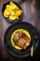 Roaster Pork Knuckle with savoy cabbage and baked potatoes - Traditional German cuisine