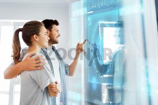 happy couple looking at futuristic virtual screen