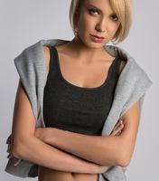 Model woman in sportswear posing indoors on gray