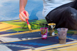 Hand with a brush. Street art. Drawing on an artistic scene in the city. Male hand with brush.