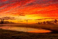 Blazing red sunrise skies across rural landscape Australia