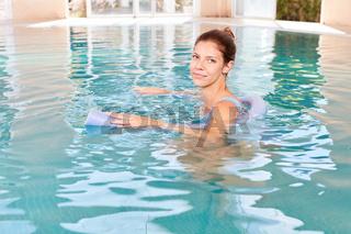 Frau im Swimmingpool mit Schwimmhilfe