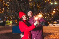 Outdoor portrait of young couple lighting sparkles