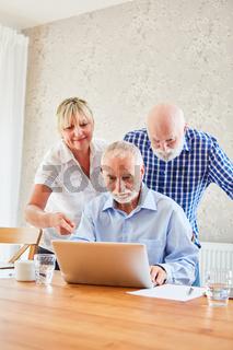 Pflegekraft betreut Senioren im Computerkurs