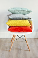 Chair in an interior with pillows in trendy colors