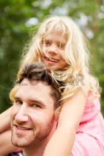 Vater mit blondem Mädchen huckepack