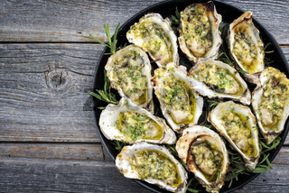 Barbecue overbaked fresh opened oyster with garlic and herbs offered as top view on a tray with copy space left