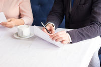 Three business people sign agreement at restaurant