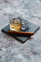 Glass of whiskey with ice cubes and cigar