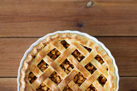 close up of apple pie in mold on wooden table