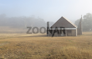 Log hut in Snowy Mountains with early morning fog