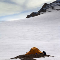 Hiker sitting near camping tent in evening snowy mountains