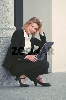 Young businesswoman using laptop at office building