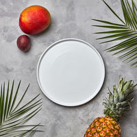 Composition from an empty white plate of green palm leaves, pineapple, mango and passion fruit on a gray marble table with a copy space.