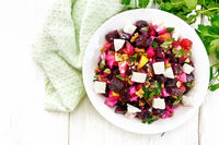 Salad with beetroot and feta in plate on board top
