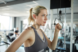 Junge Frau trainiert Trizeps Muskel am Kabelzug