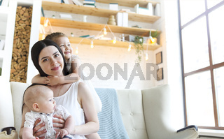 Happy mother and cute little kids spending time together and smiling at camera