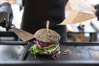 Chef preparing burgers at grill plate on international urban street food festival.