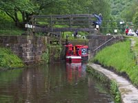 a group of people taking a narrowboat though a lock gate on the rochdale canal in hebden bridge west yorkshire