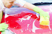 Man in green gloves washing car with yellow sponge. Place for text
