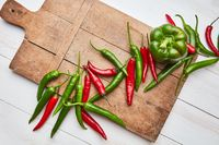 wooden board with colorful peppers and green paprika on a white wooden background
