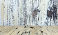 old painted washed oak wood table on the blurry white wood wall background, wooden table.