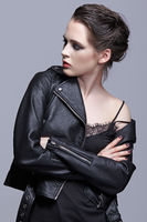 Portrait of female in black leather jacket. Woman with unusual beauty evening makeup and violet - black shadows make-up.