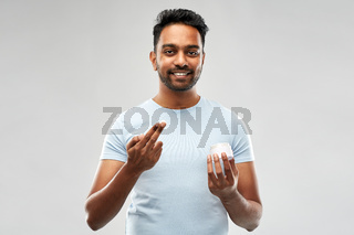 happy indian man applying cream to face