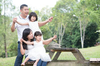 Happy Asian family at outdoor with empty table space.