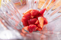 fresh ripe slice strawberry in a glass blender , close up. Flat lay
