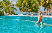 Toddler boy in resort swimming pool